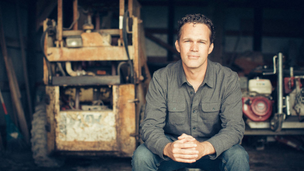 Dr. Zach Bush sitting with hands clasped facing camera on the Evolving Man Podcast